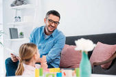 selective focus of father looking at daughter playing with colorful blocks in living room
