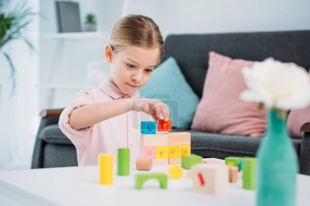 portrait of kid playing with colorful blocks in living room at home
