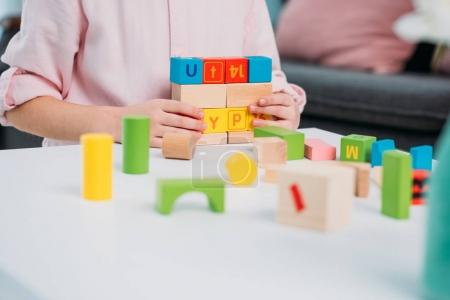 partial view of kid playing with colorful blocks at home