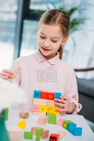portrait of cute kid playing with colorful blocks at home