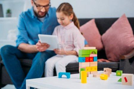 Photo pour Mise au point sélective de père et fille avec tablette ensemble à la maison - image libre de droit