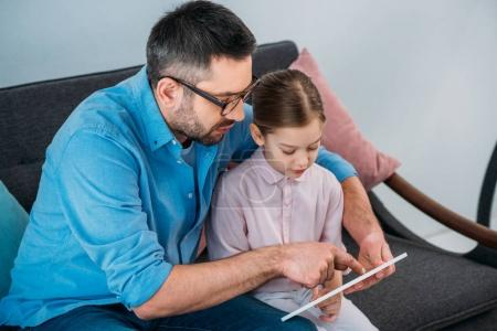 father and daughter using tablet together at home