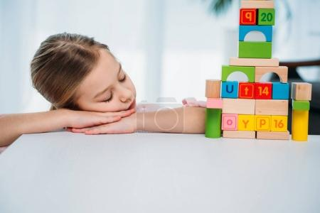 child sleeping on table with pyramid made of colorful blocks
