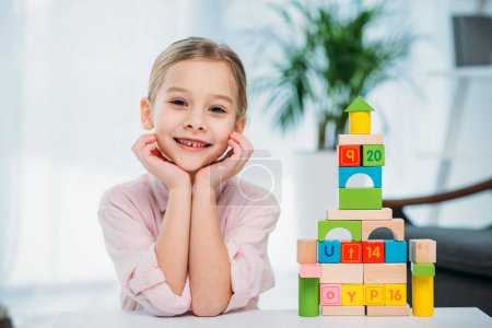 Photo for Portrait of smiling kid near pyramid made of colorful blocks on table - Royalty Free Image