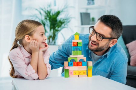 portrait of family looking at each other near  pyramid from colorful blocks at home