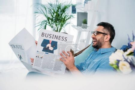 happy man and daughter reading newspapers while resting on sofa at home