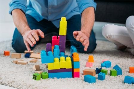 partial view of kid and father playing with colorful blocks together on floor at home