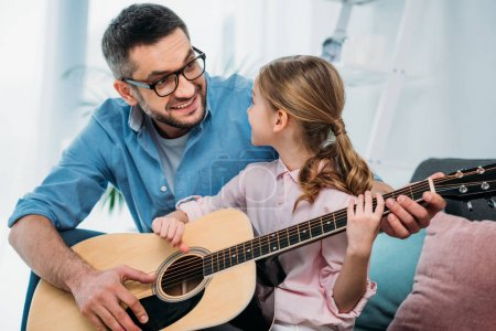 father teaching daughter play guitar at home