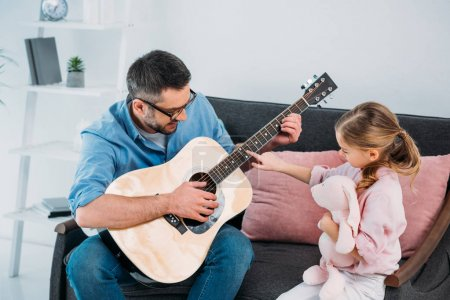 man playing acoustic guitar for daughter in living room