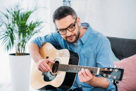 Photo pour Portrait d'un homme à lunettes, jouer de la guitare acoustique à la maison - image libre de droit