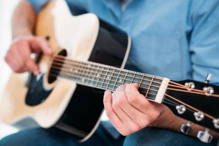 Photo for Cropped shot of man playing acoustic guitar at home - Royalty Free Image