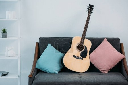 close up view of acoustic guitar on sofa with pillows in living room