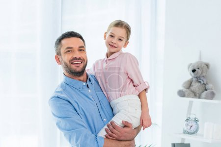 portrait of happy father holding little daughter in hands at home
