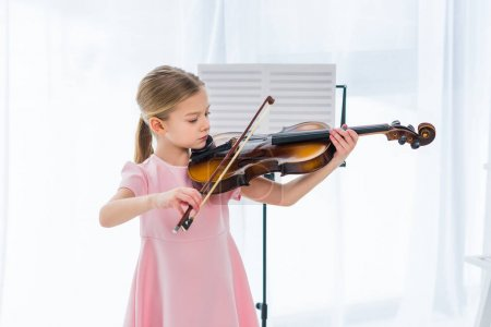 Photo for Cute little child in pink dress playing violin at home - Royalty Free Image