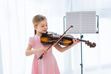 smiling little child in pink dress playing violin at home