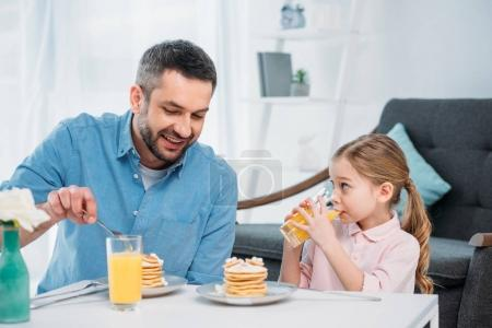 smiling father and little daughter having breakfast at home
