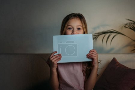 obscured view of little kid with tablet at home