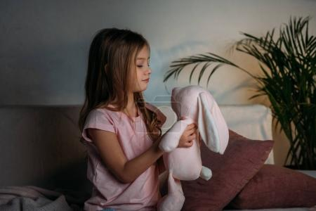 side view of cute kid with toy resting on sofa