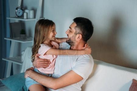 Photo pour Vue latérale du souriant père et fille en regardant l'autre à la maison - image libre de droit