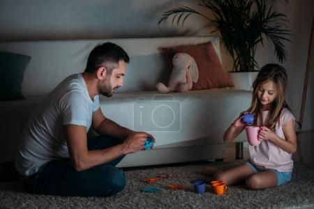 father and daughter pretending to have tea party together at home