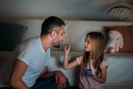 Photo for Father and daughter pretending to have tea party together at home - Royalty Free Image