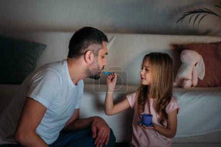 Photo pour Père et fille prétendant avoir goûter ensemble à la maison - image libre de droit