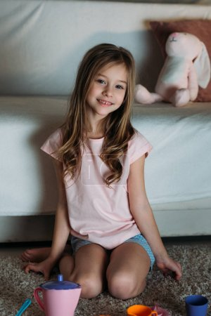 smiling little kid sitting on floor with tea party toys at home