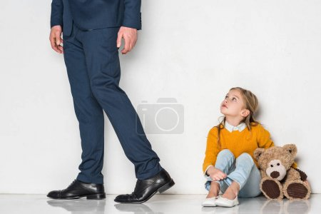 Photo for Upset daughter looking at father in business suit walking away isolated on grey - Royalty Free Image