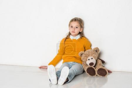 little kid with teddy bear looking at camera while sitting on floor