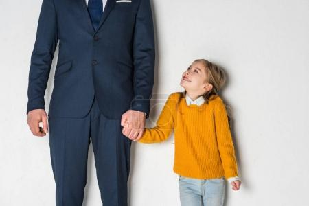 Photo for Partial view of sad daughter and father in business suit holding hands isolated on grey - Royalty Free Image