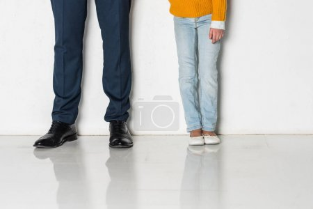 partial view of daughter and father in business suit holding hands isolated on grey
