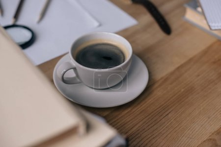 close-up shot of cup of coffee on work desk with stack of books