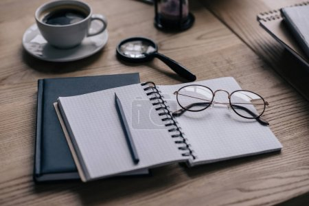 close-up shot of notebooks and cup of coffee on work desk