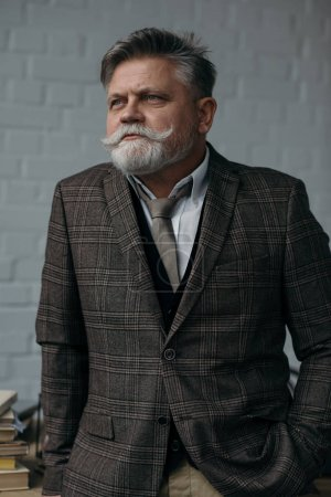 senior man in stylish tweed suit looking away in front of white brick wall