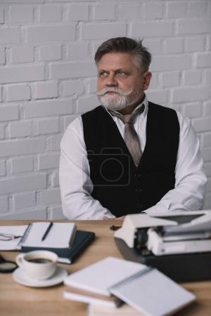 thoughtful senior writer sitting at workplace against white brick wall