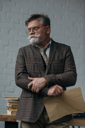 senior man with sheet of kraft paper looking away at workplace