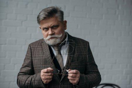 serious senior man in tweed suit looking at camera