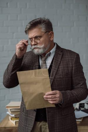 senior writer in tweed suit and eyeglasses with letter near workplace