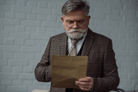 thoughtful senior man with pencil and sheet of paper in front of white brick wall