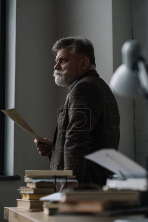 thoughtful senior writer with manuscript looking away