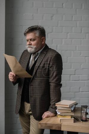 senior man reading letter while leaning at work desk
