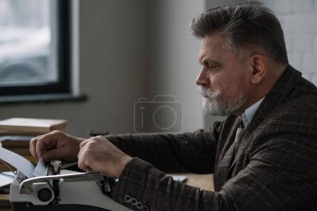 handsome senior writer loading paper into typewriter