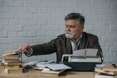 senior writer at workplace taking book from stack