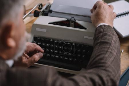 close-up shot of writer loading paper into typewriter