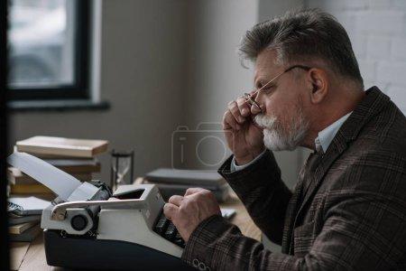 Photo pour Concentré de rédacteur principal fonctionne avec la machine à écrire - image libre de droit