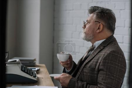 handsome senior writer in tweed suit drinking coffee at workplace