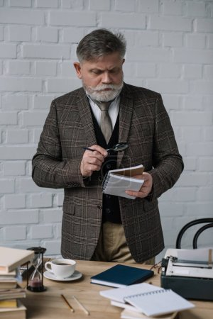 focused senior writer reading manuscript with magnifying glass