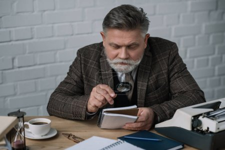 handsome senior writer reading manuscript with magnifying glass