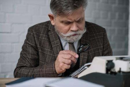 bearded senior writer reading manuscript with magnifying glass