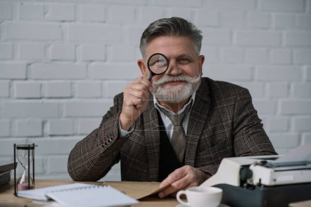 senior writer looking at camera through magnifying glass